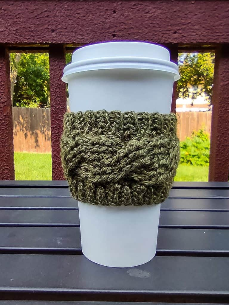 green cable cup cozy on white disposable coffee cup