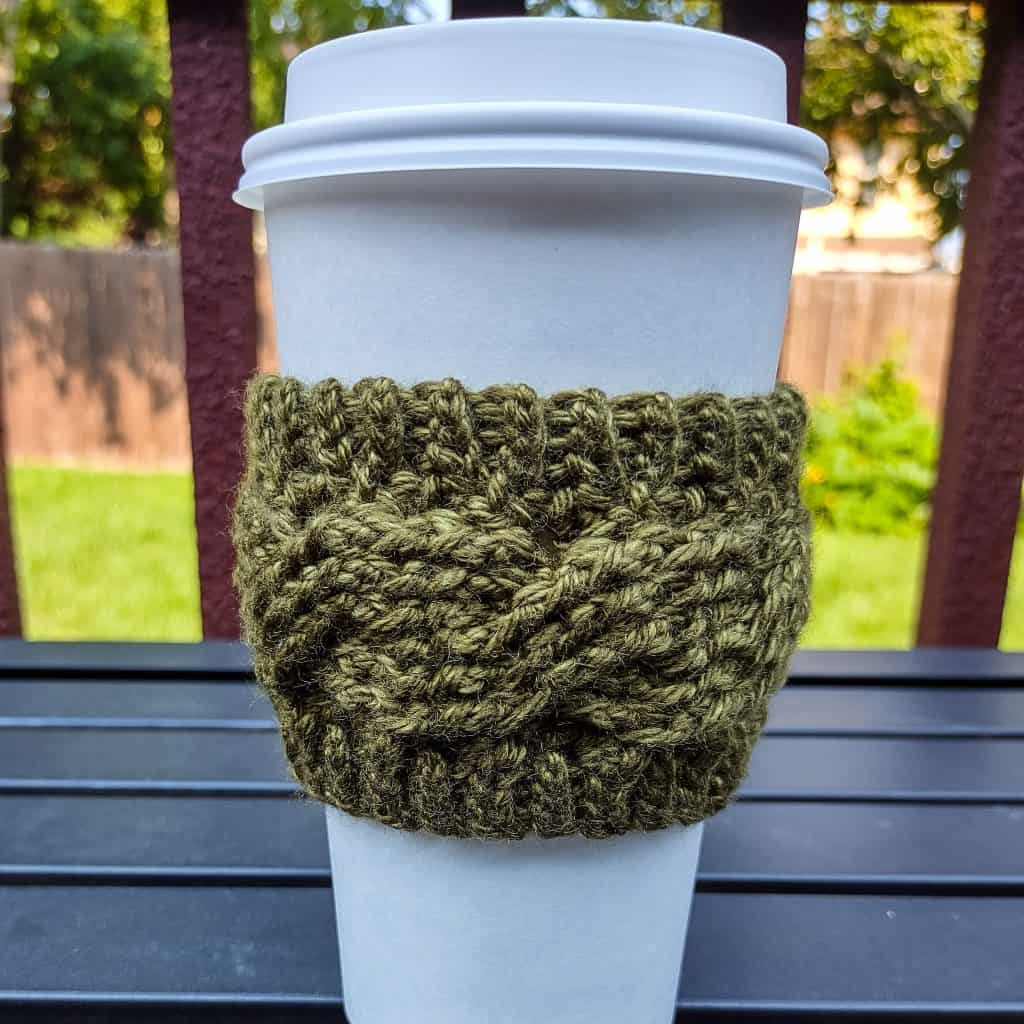green cable crochet cup cozy on white coffee cup